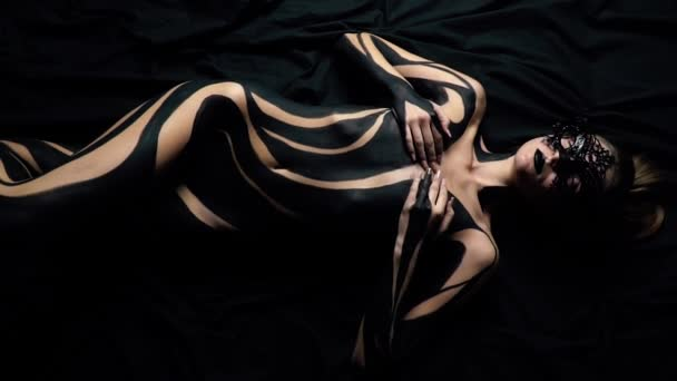 A girl in a lace mask and black body art lies on a black sheet