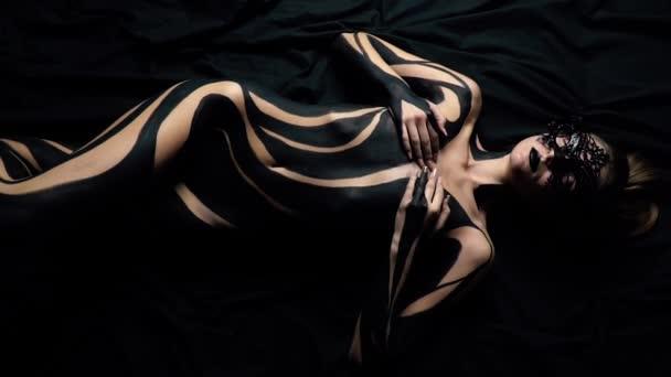Dívku v krajkové masky a černé body art leží na černý list