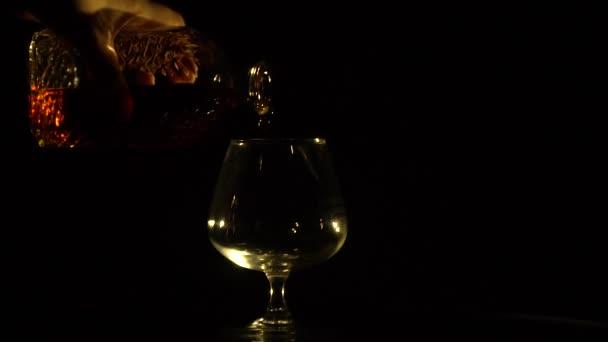 Egy kéz önti a decanter a cognac egy pohárba