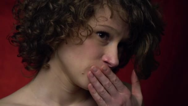 Confused girl is nervous covers her mouth with her hand