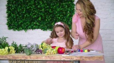 Anya és lánya, rózsaszín ruhákat felhívni a ceruza között a virágok és gyümölcsök a stúdióban florisztika