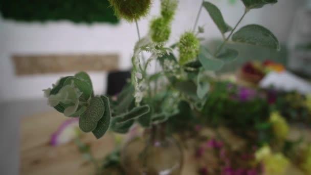 Květiny ve váze a asi na stůl roztroušených zelení