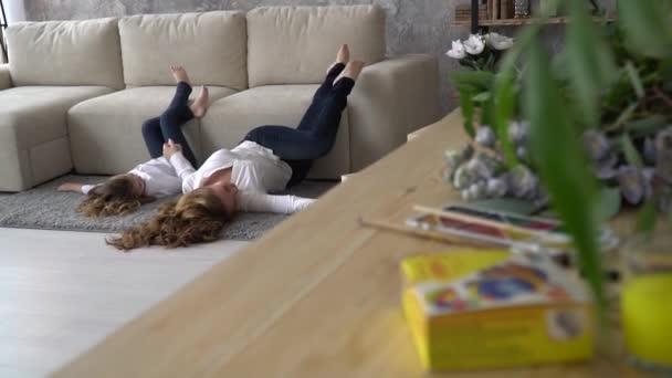 Anya és lánya szórakoznak feküdt a szőnyegen, az asztalon hazugság virágok és festékek