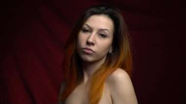 An arrogant woman with red hair looks at the camera, slow motion