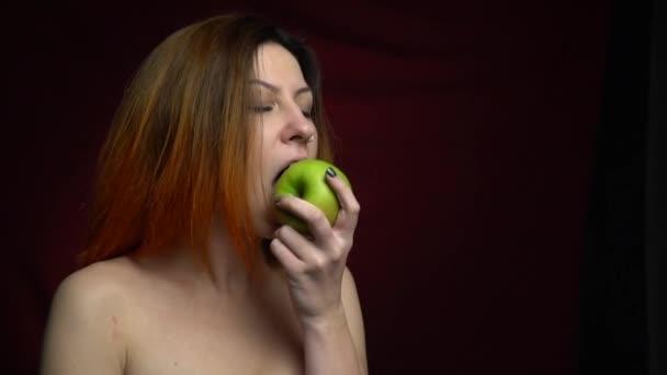 Žena hovoří yammy a kouše zelený, šťavnaté jablko