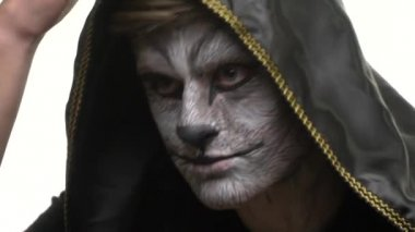 Body Art Raccoon on the face of a guy who looks at his friend at point blank range. Animal Make up