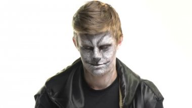 Body Art Raccoon on the face of a guy who sits on a white background and looks at the camera. Animal Make up