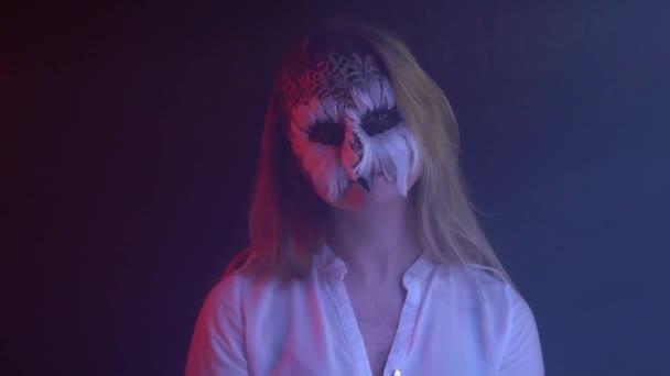 Gufo di arte di corpo della ragazza sul suo viso, che gira la testa in direzioni diverse e la sua luce blu e rossa brilla su di lei. Animale Make-up