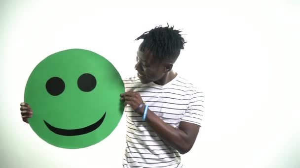 A young black man with bracelets is holding a green smiley that smiles then turns on a sad