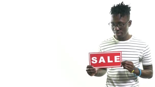 Black man in glasses pointing with finger on sales sign and showing thumbs up, slow motion