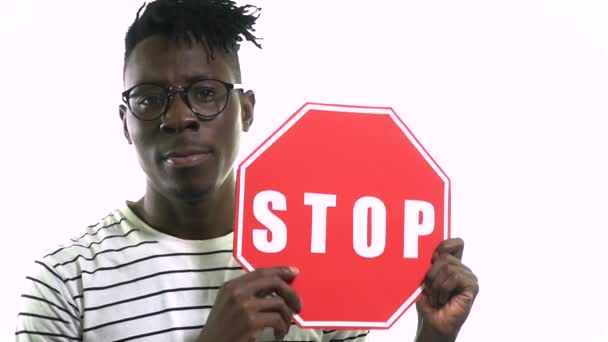 Serious black man in hipster glasses holding a red stop sign