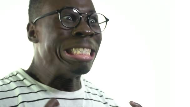 A black man with a small beard in his glasses screams with anger