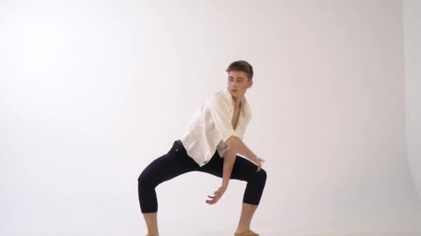 A slender ballet dancer is dancing on a white background, slow motion