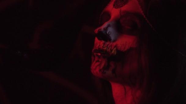 Čert s rohy a krev na jeho rtech vypadá v profilu, malování těla