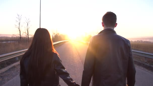 A loving couple is walking along the road in the sunset, slow motion