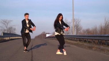 A pair of dancers dance the ballet on the road, an deor. Slow motion