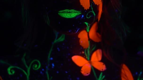 Dívka s zelené rty a oranžové motýlů na jejím těle sexuálně kouše rty