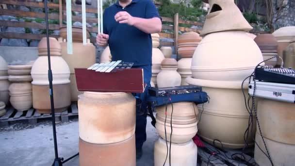 Člověk vyladí své hudební nástroje před hraním v atmosférické obchodě hliněné hrnce