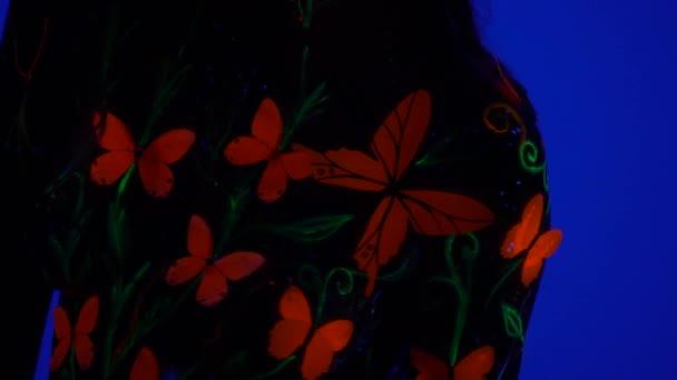Dlouhá chlupatá žena v osvětlený bodyart pózuje ve tmě na modrém pozadí