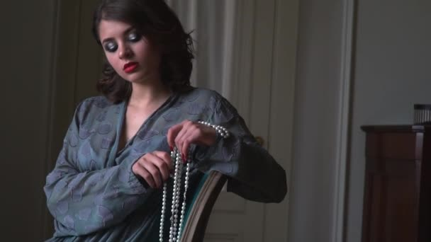Dívka s perlou náhrdelník sedí v křesle