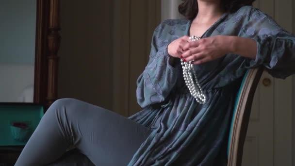 Dívka sedí v křesle v časných ranních hodinách a drží ve své ruce ozdoby