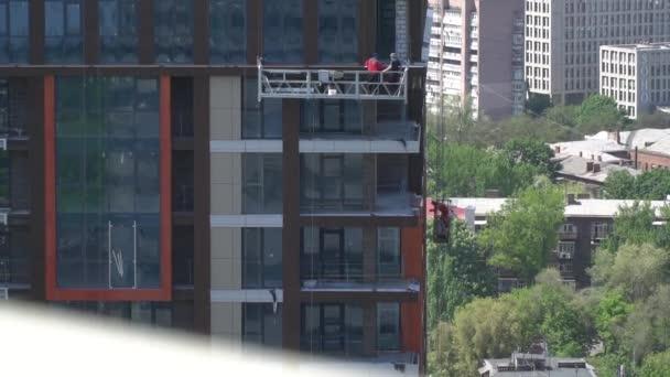 Muži stavitelé v jejich výšce stavět mrakodrap, pomalý pohyb