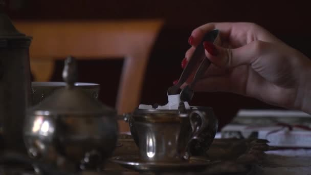 Dívka staví kostky cukru do svého čaje, pomalý pohyb