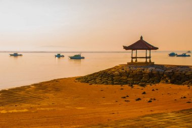 Balinese boats and pavilion in Sanur beach in the morning at dawn, Bali, Indonesia.