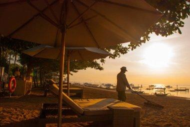 Beautiful dawn on the beach in Sanur. Worker cleans the beach.