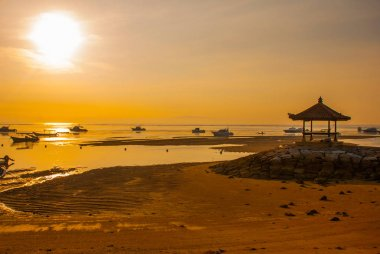 Traditional Balinese boats and pavilion in Sanur beach in the morning at dawn, Bali, Indonesia.