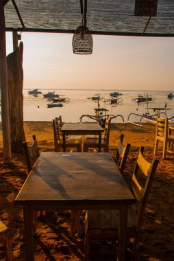 Beautiful beach with a cafe in Sanur with local traditional boats. Bali, Indonesia. Dawn.