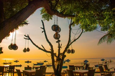 Beautiful beach with a cafe in Sanur with local traditional boats. Bali. Indonesia