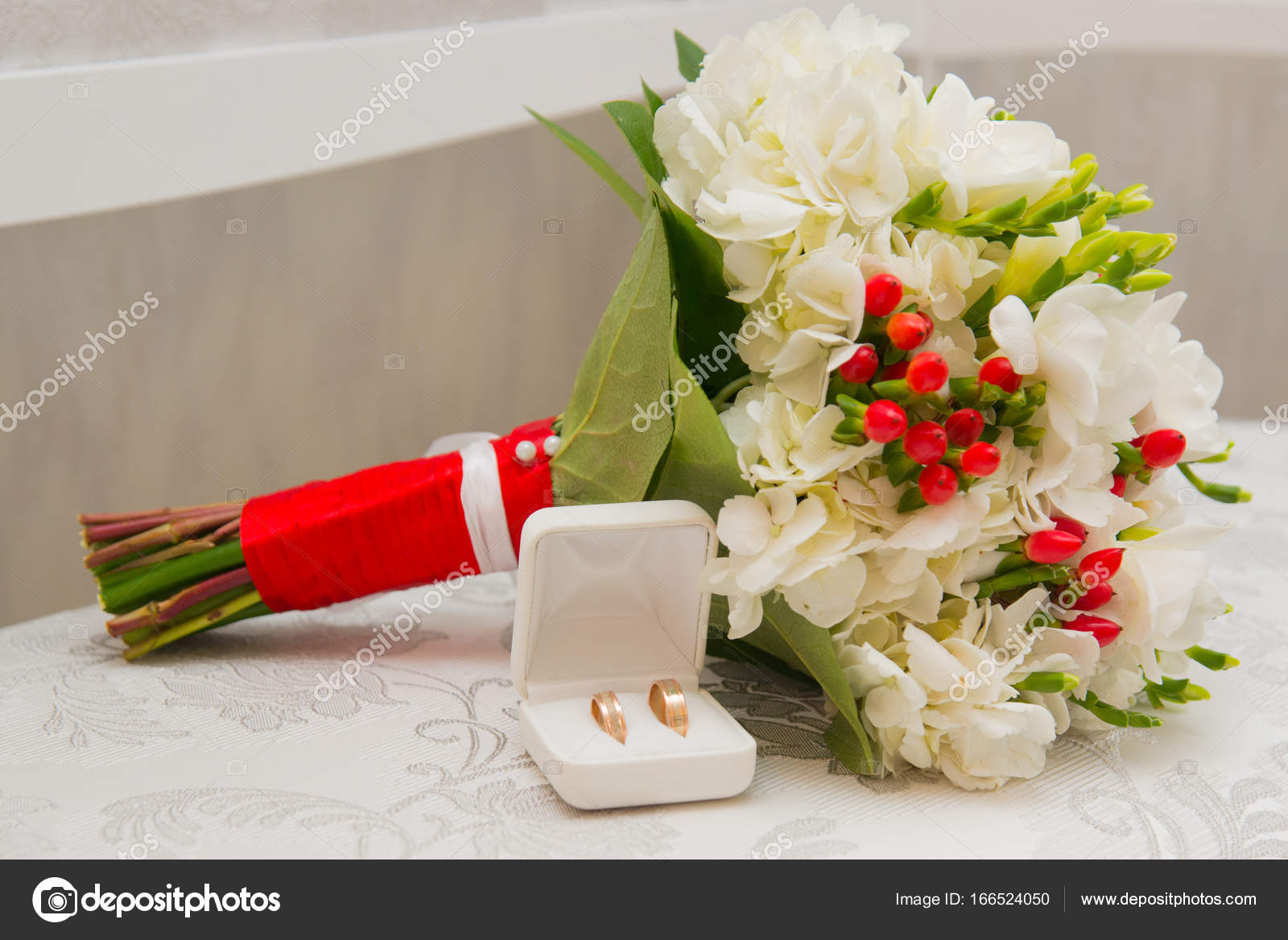 Two Golden Wedding Rings In White Box And Bouquet With White Flowers