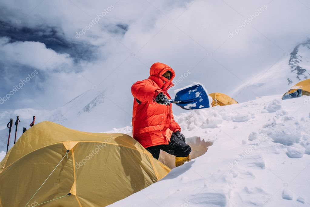 man cleaning tent of snow