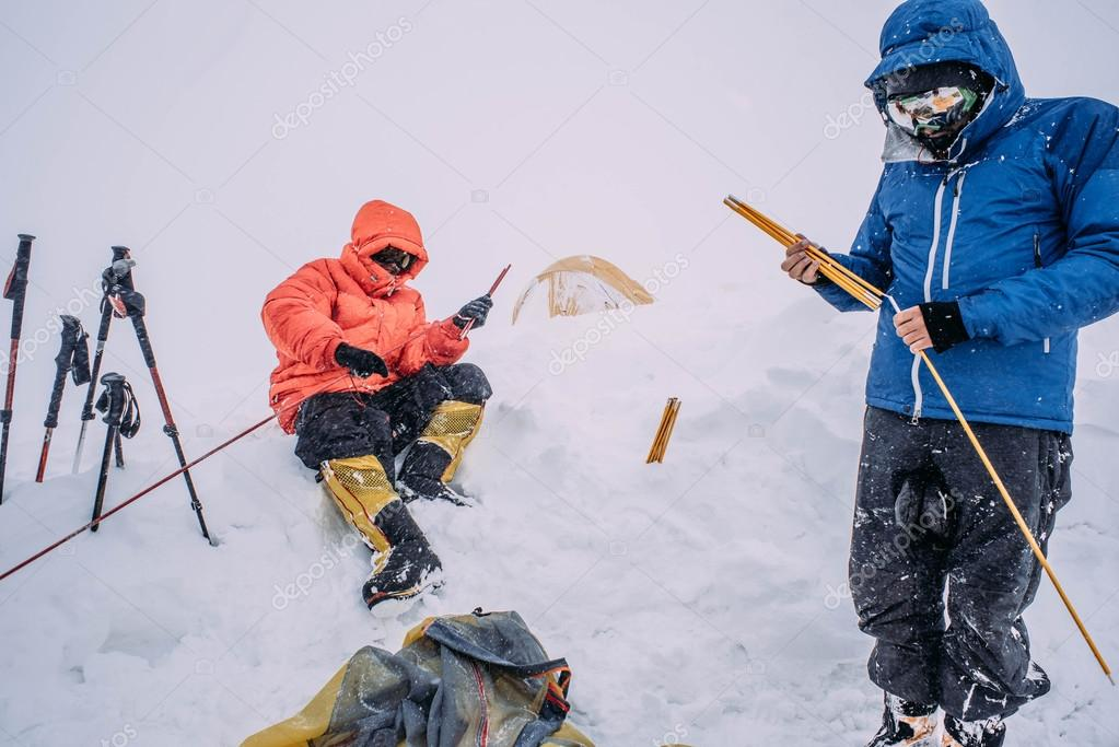 alpine climber men in heavy storm in mountains