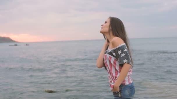 Mladá krásná žena na pláži během východu slunce s vlajkou Usa. 4. července koncept