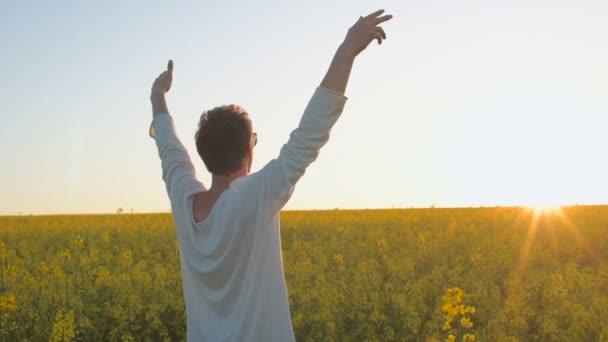 Happy young man have fun in yellow green rape meadow