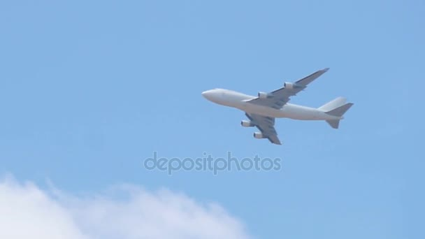 Close up of white cargo airplane passing on blue sky