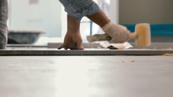 Cinemagraph pracovníka uvedení keramik dlaždice na podlaze. Mu stiskne dlaždice na podlahu s dřevěné kladivo.