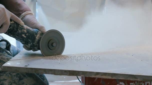 dělník, řezání dlaždic pomocí úhlové brusky na staveništi.