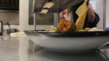 Timelapse of a busy team of chefs and waiters and kitchen staff preparing and serving food in a commercial kitchen.