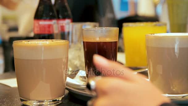 Sok szemüveg, kávé és gyümölcslé kerülnek a pultra egy kávézóban. Pincérnő veszi a szemüveg.