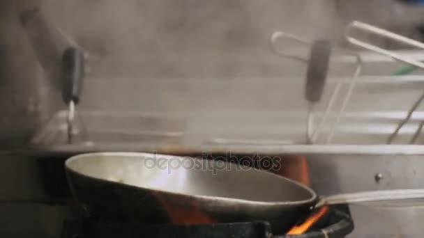 Kuchař je míchání zeleninu na pánvi.