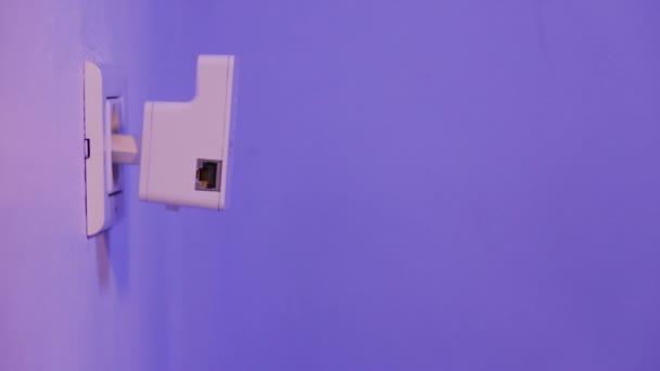 Muž s lakováním prst na tlačítko Wps na Wifi opakovač, který je do zásuvky na zdi. Zařízení pomoci rozšířit bezdrátovou síť doma nebo v kanceláři.