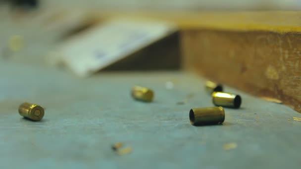 Leere Pistolenkugeln fallen und schlagen auf einem Schießstand auf einem Holztisch ein. Extreme Nahaufnahme, selektiver Fokus mit unscharfem Hintergrund und Kopierraum.