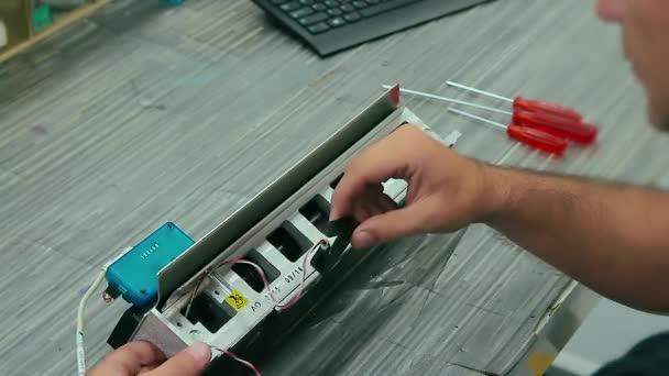 Elektrikář montuje elektrická zařízení do stroje v továrně. Zblízka na izraelský kavkazský muž inženýr spojující elektrické dráty.