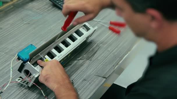 Cinemagraph of electrician montuje elektrická zařízení do stroje v továrně. Smyčka zblízka na izraelský kavkazský muž inženýr šroubuje šroubem se šroubovákem.