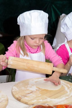 little girl in chefs hat is cooking pizza