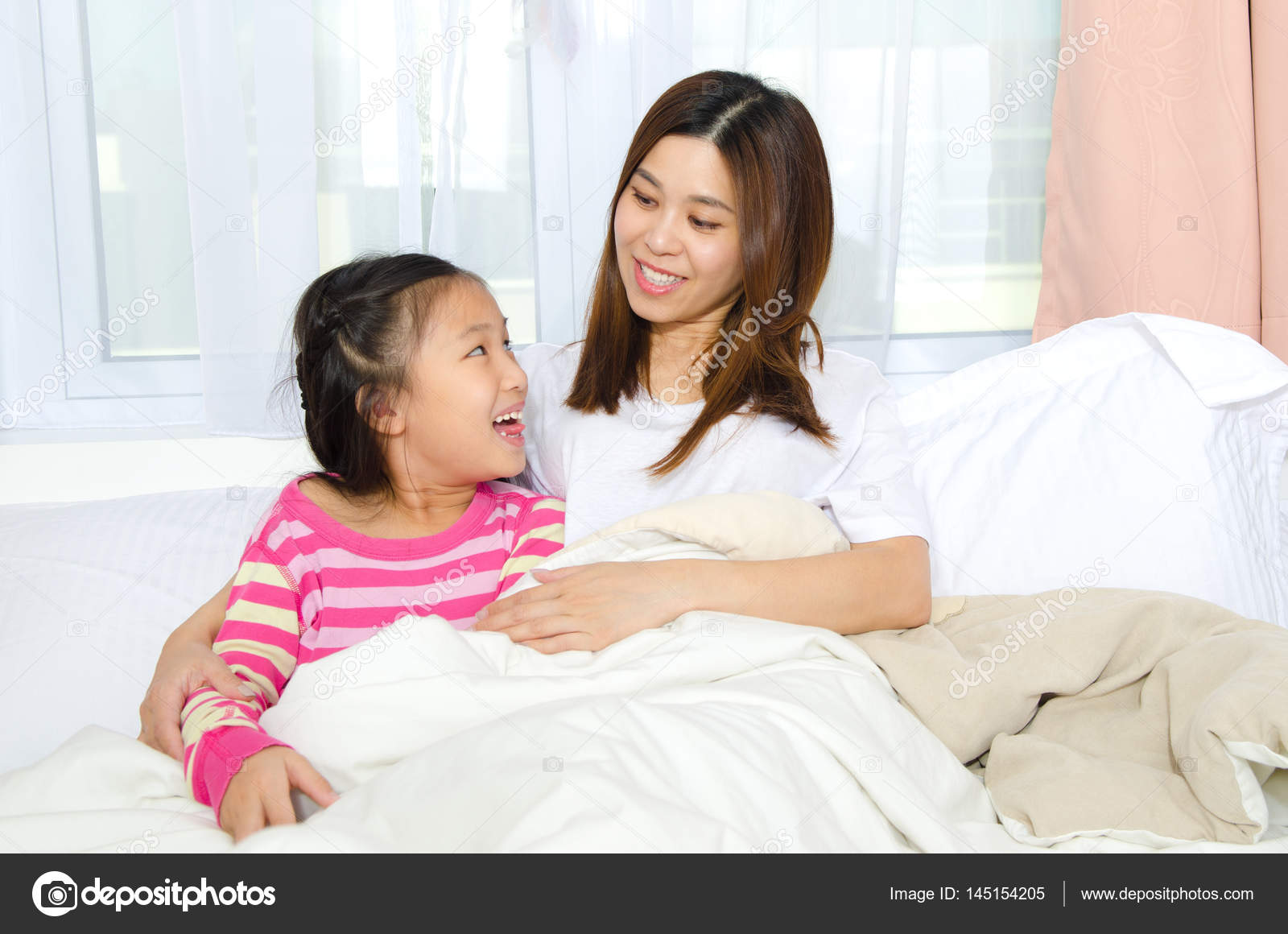 Asian mother and daughter bonding time on the bed — Photo by ...