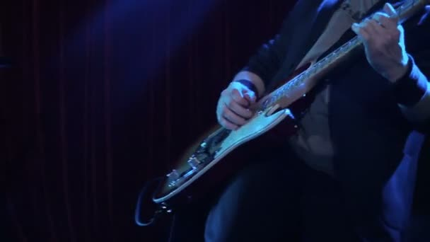 Man playing rock song on electric guitar in night club. close-up. Musician play wooden electric guitar on stage